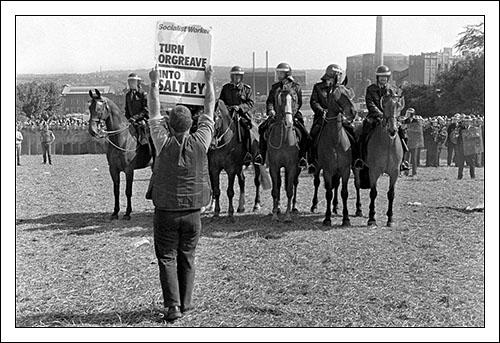 "Postcard of a picket holding placard reading ""Turn Orgreave into Saltley"" on 18th June 1984."